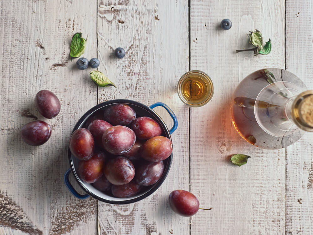 Traditional serbian plum brandy and plums on wooden table. Top view.