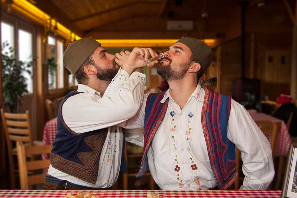 Two Men With Beards, Friends, Dressed in Serbian National Costumes, Having Fun Drinking Traditional Drink.