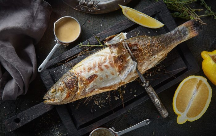 Grilled Sea Bass on a Wooden Board With Sauces, Lemon Slices and Herbs